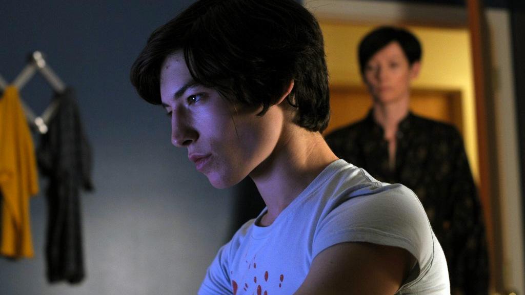 Un adolescente mira su computadora mientras su madre lo observa desde la puerta de su habitación.