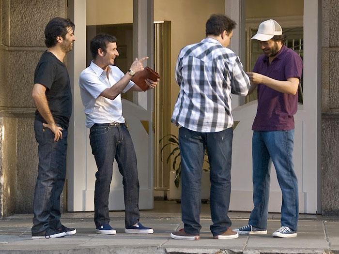 Cuatro amigos se encuentran en el portal de un edificio