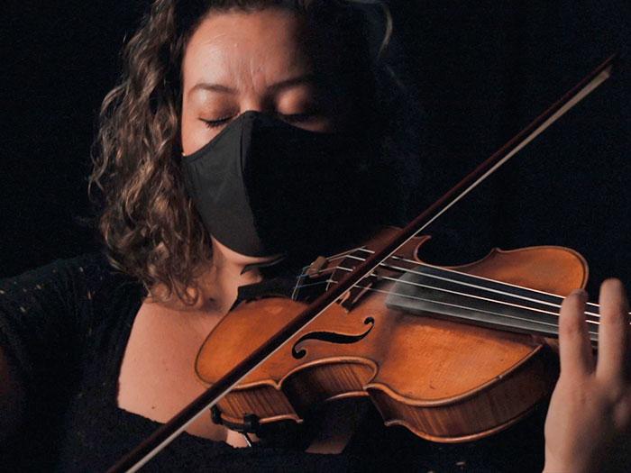 una mujer con tapabocas de la sinfonica nacional toca el violonchelo en la serie contra el olvido