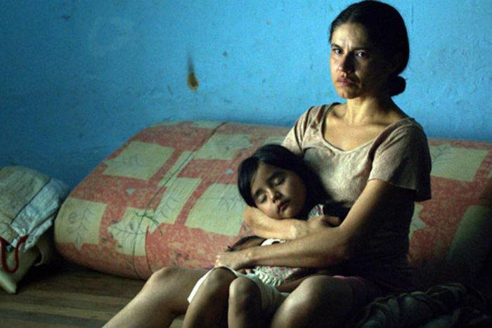 Una mujer y su hija reposan en un cuarto semi vacío