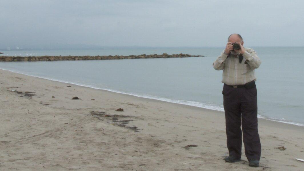 hombre de la tercera edad en la playa tomando una foto
