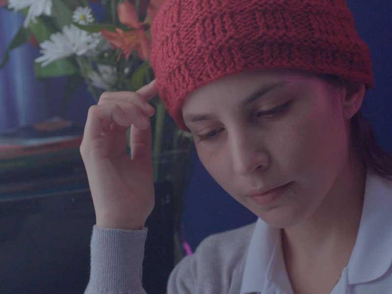 Una chica joven se ve pensativa en su cuarto en Los diarios secretos de las chicas incompletas