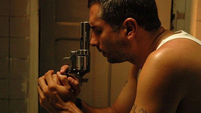 hombre sostiene un arma apuntando a su cabeza en la película perro come perro