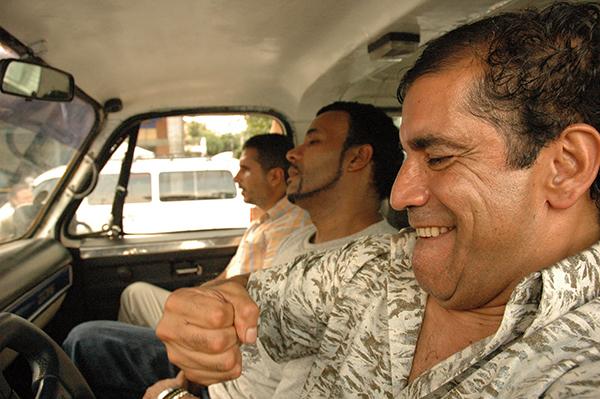 tres hombres armados en una camioneta vieja en la película perro come perro