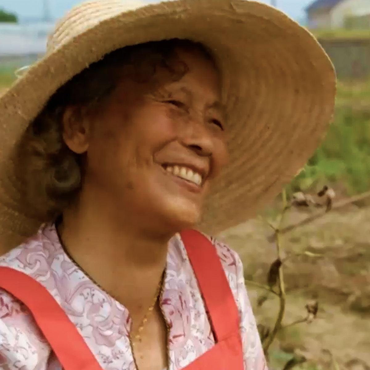 mujer china de la tercera edad en un campo chino