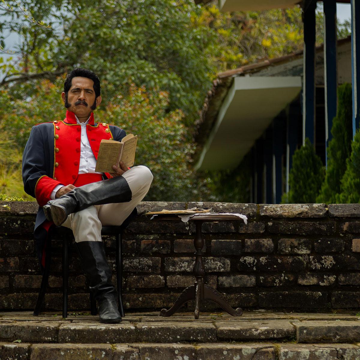 hombre con ropa militar colonial sentado en una hacienda