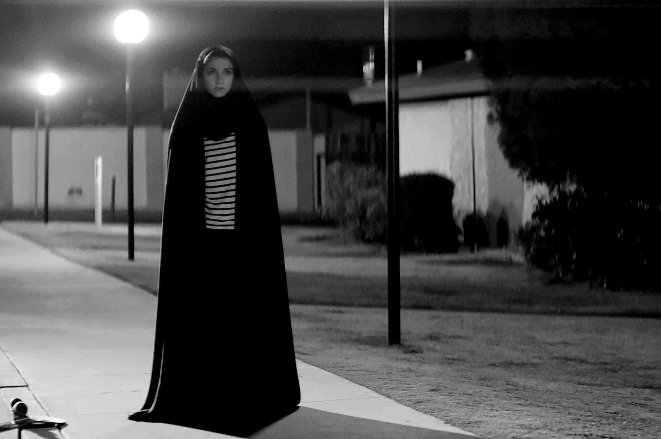 Una mujer iraní camina en una noche oscura