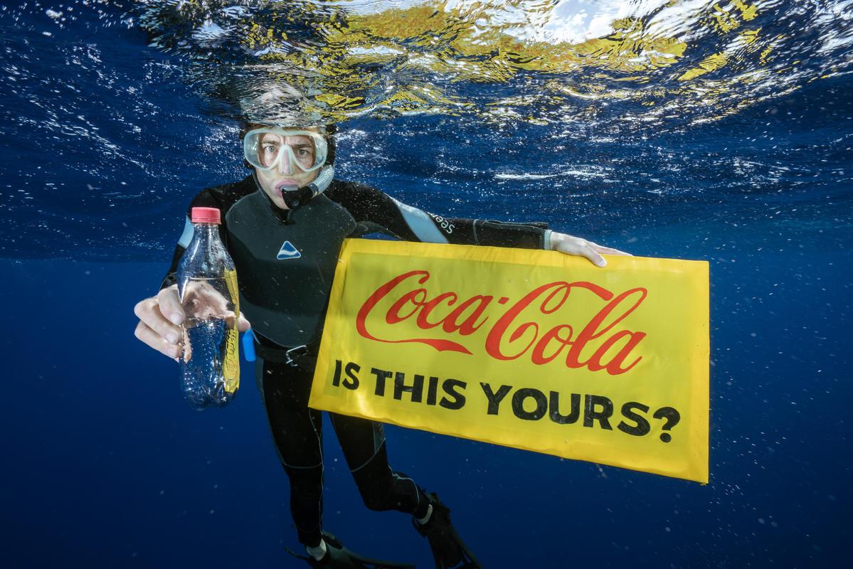 """Un buso con una botella plástica en la mano pregunta con un cartel """"¿Cocacola, esto es tuyo?"""""""