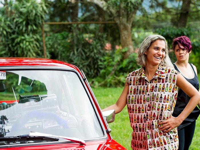 dos chicas jóvenes al lado de un auto clásico en la película Atrás hay relámpagos