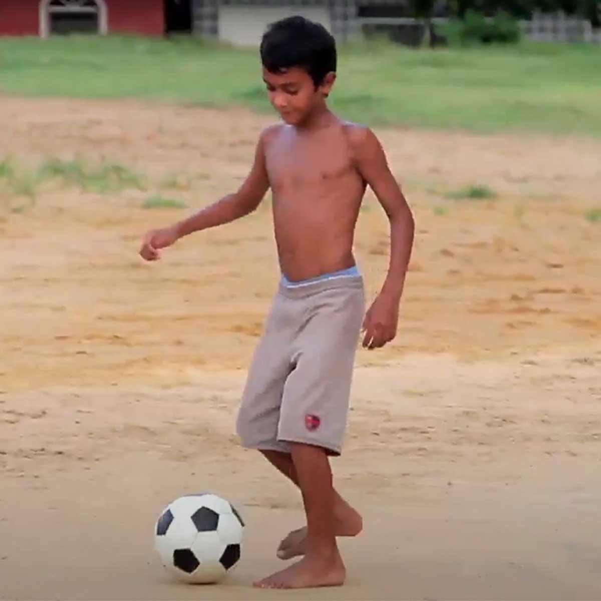 Niño jugando fútbol en terreno sin pasto
