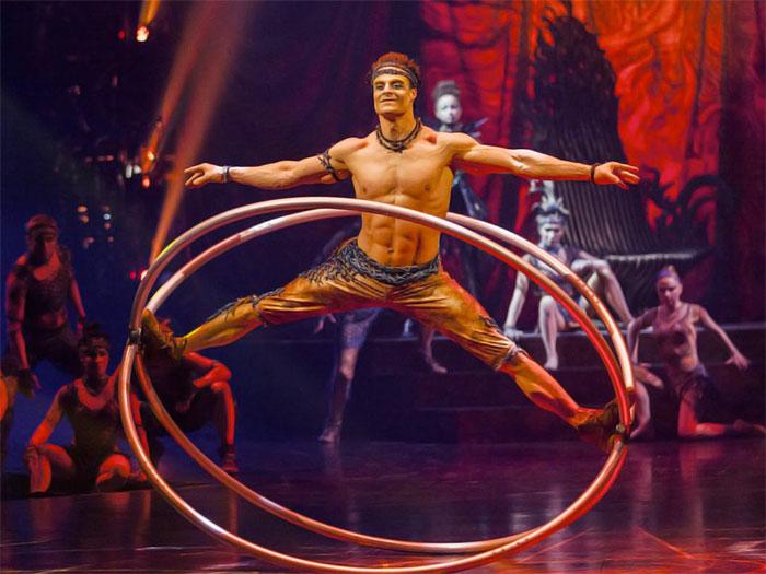 Un hombre haciendo acrobacias con aros de metal en espectáculo del Circo del Sol