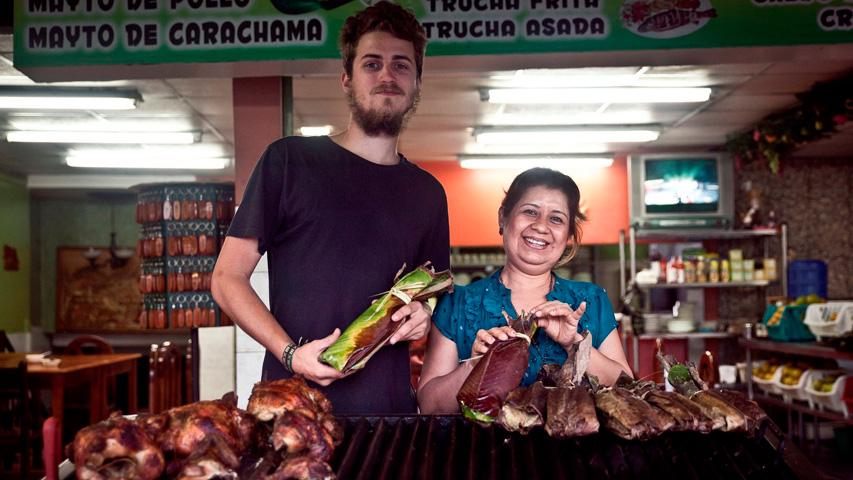 Cocineros en el mercado, soteniendo envueltos de maíz.