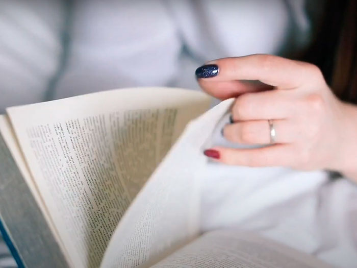 Día internacional del libro 2021, una mano de una mujer leyendo un libro