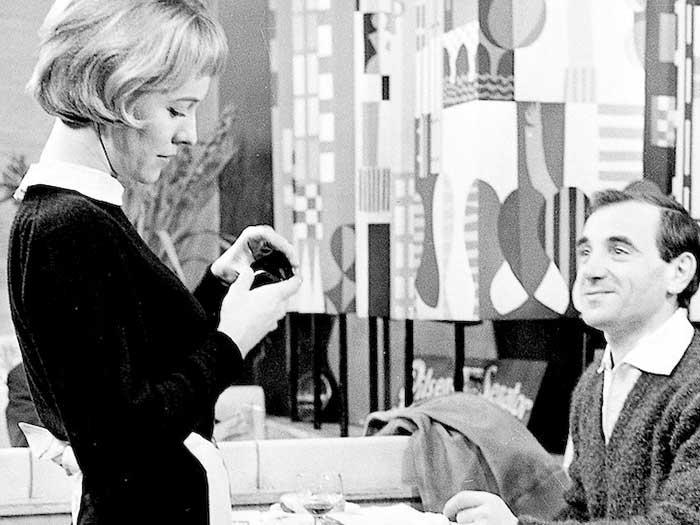 Ununa mujer y un hombre elegantes sonríen en Disparen al pianista de Truffaut