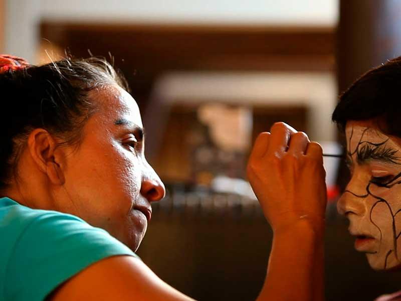 Una mujer maquilla a un niño en el documental Quijote