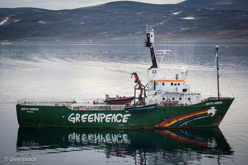 Un buzo de greenpeace recoge desechos plásticos en el mar abierto