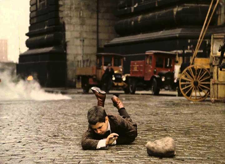 Un niño tendido en el piso porque, aparentemente, se ha caido, zona industrial, nueva york años 20