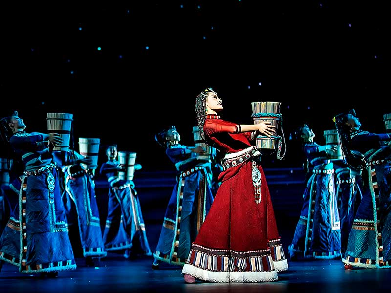 Una mujer levanta un jarrón al aire en la gala de danza del origen del rio amarillo