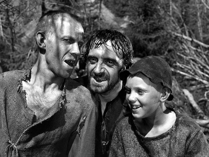 Tres hombres con traje medieval y dientes dañados en la película el manantial de la doncella