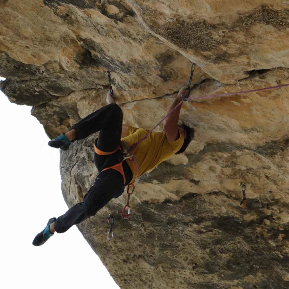 escalador suspendido por un arnés en una montaña