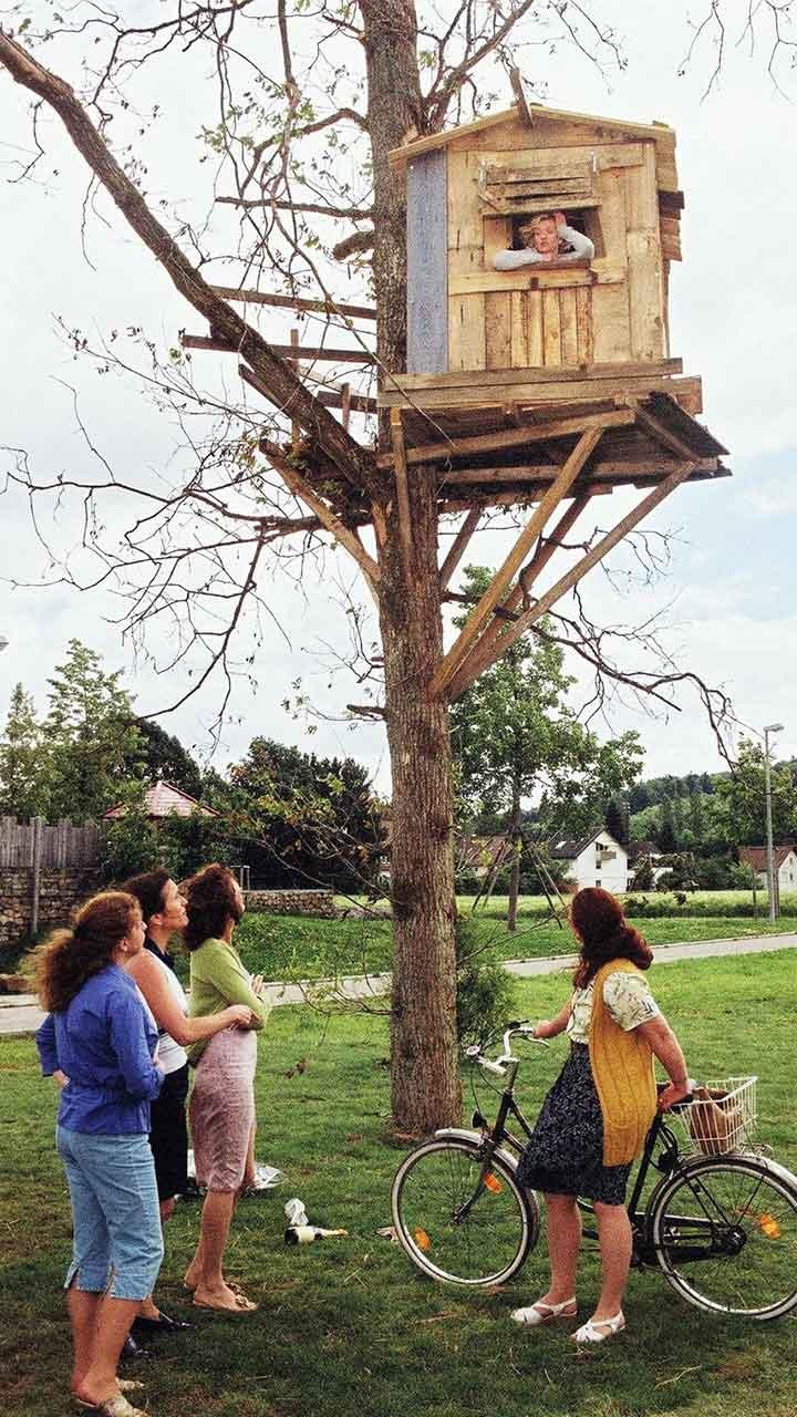 Una mujer dentro de una casa de árbol es observada por otra mujeres desde el piso en la pelicula alemana out on a limb