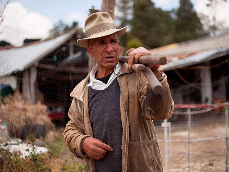 Campesino con ruana sostiene una pala en el documental Sumercé