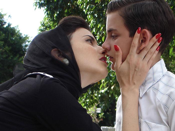 Una mujer besa a un niño en la mesa en La edad de la peseta