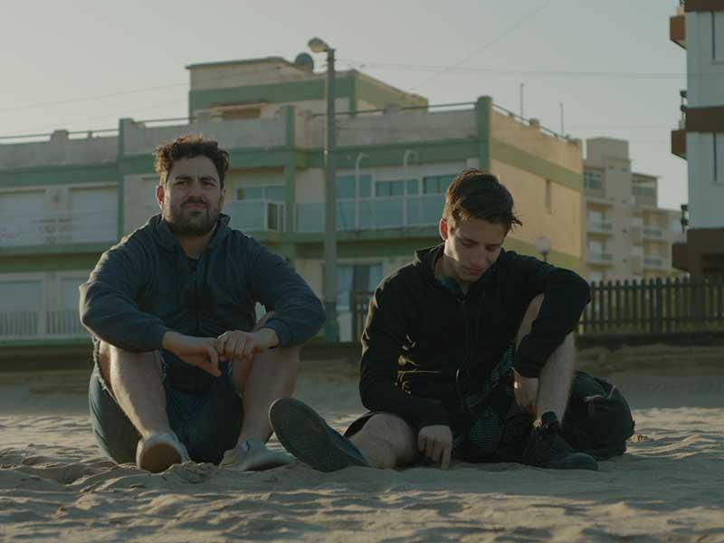 Un padre y su hijo hablan en la playa, en la película Las Vegas