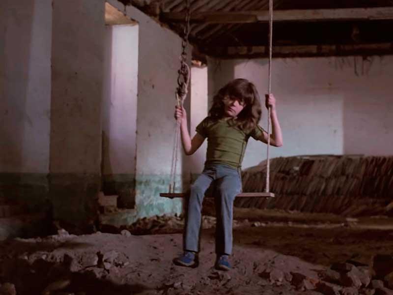 Un niño juega sólo en un patio trasero en la película El muro del silencio