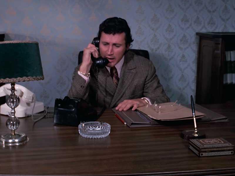 Un hombre habla por teléfono en la película El muro del silencio