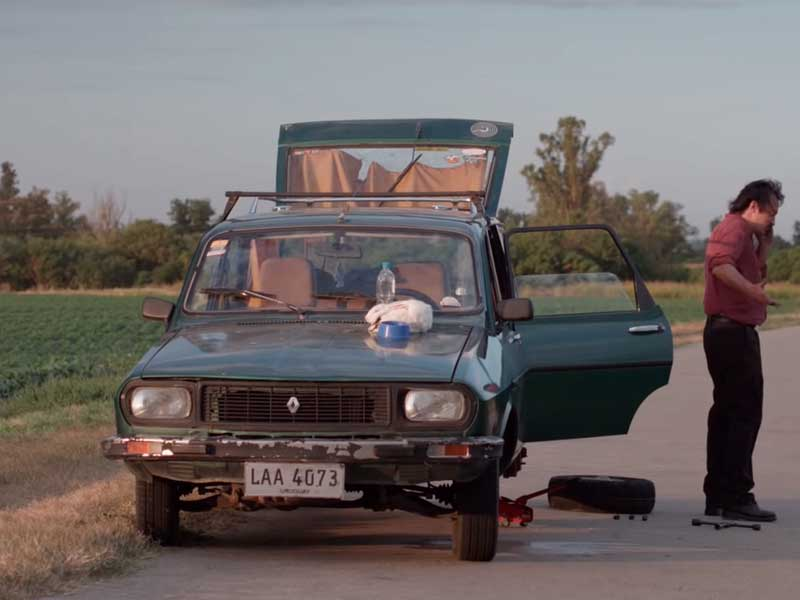 Una hombre intenta arreglar un carro viejo en la película Una noche sin luna