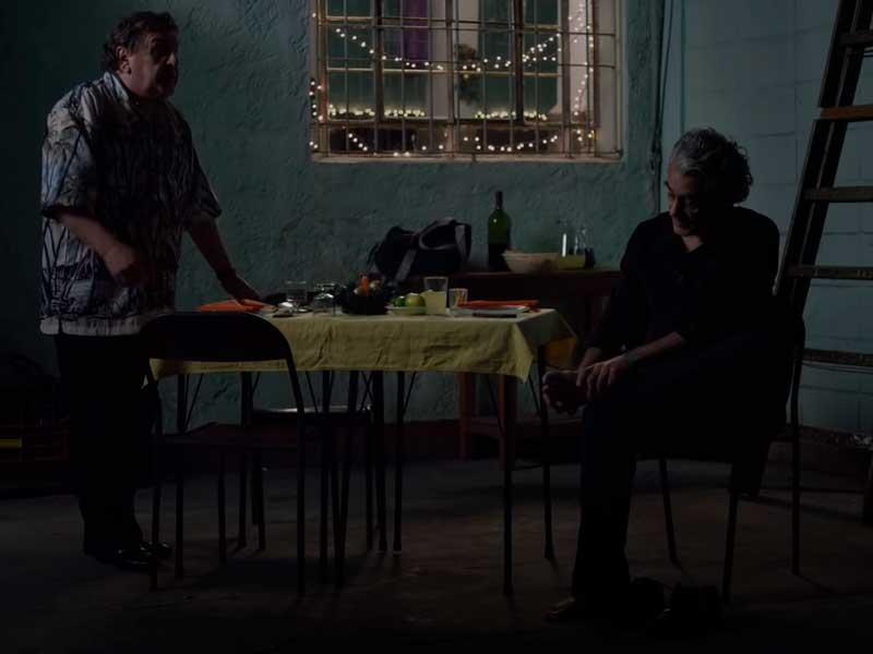 Dos hombres hablan alrededor de una mesa en la película Una noche sin luna