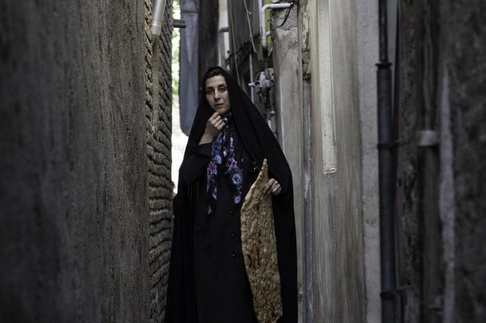 Una mujer iraní con cara afligida posa en un callejón oscuro en luz día
