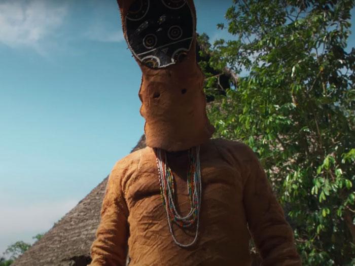 Indígena del Amazonas cubierto en un traje tradicional