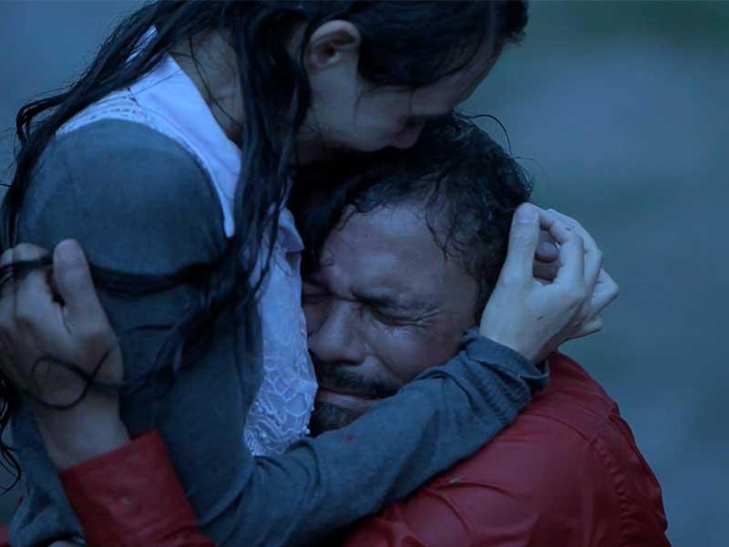 Una pareja se abraza mientras llora bajo la lluvia en la serie Vía crucis