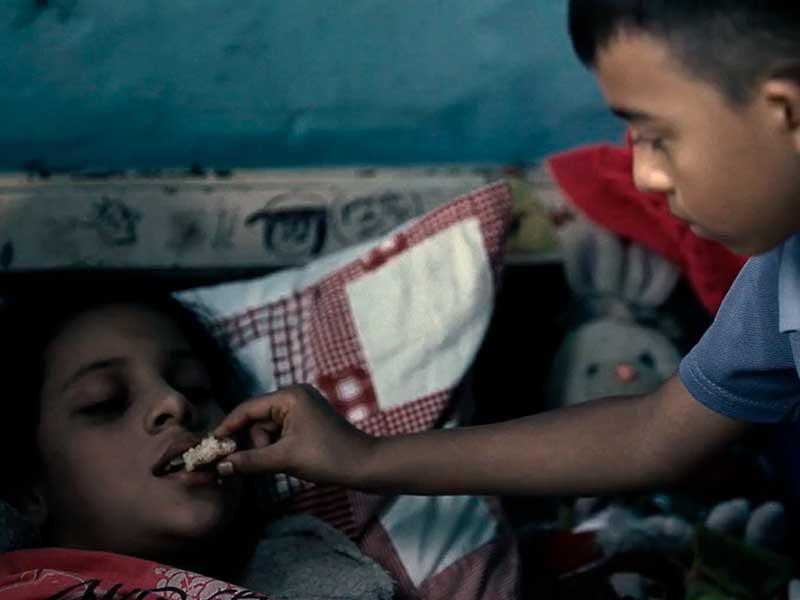 """Un niño alimenta a una niña enferma en """"Vía crucis"""""""