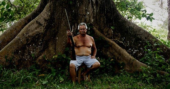 Un hombre mayor se sienta en las raíces de un árbol con un arma en la mano.
