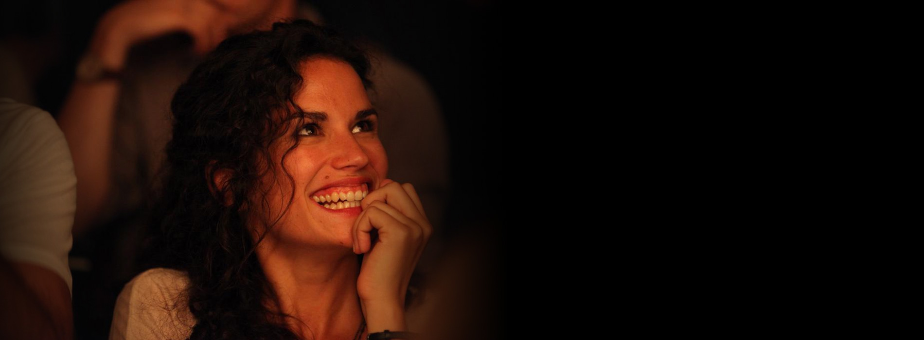 Una mujer joven de pelo rizado sonríe.