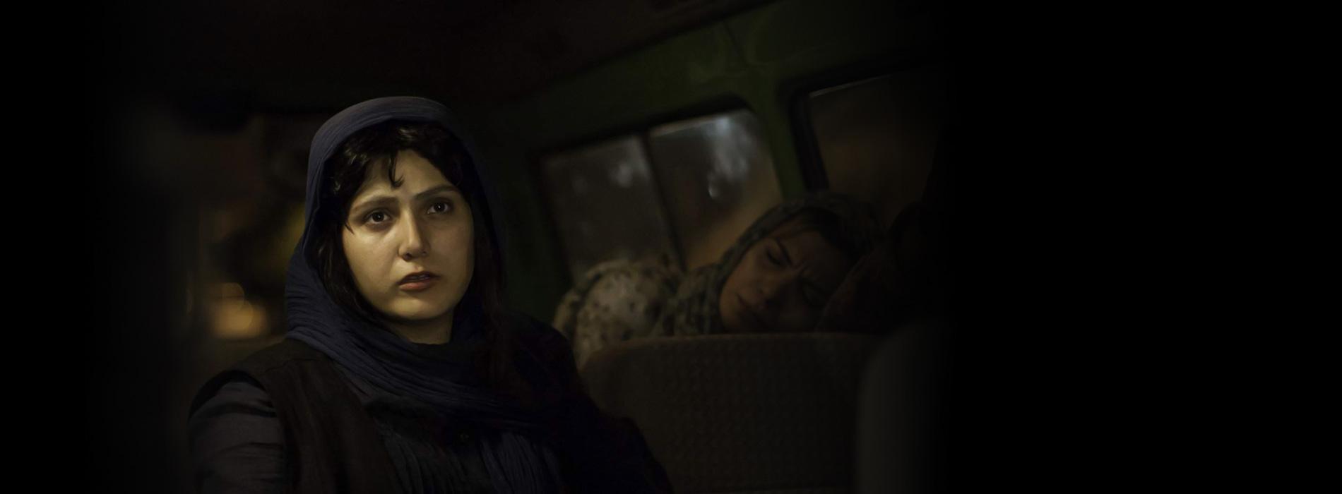Una mujer iraní se ve preocupada al interior de un autobús.