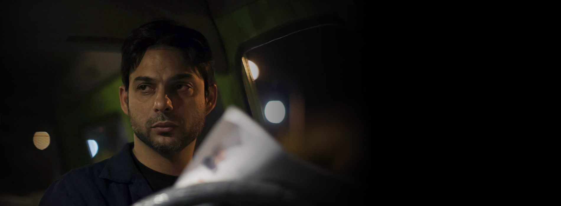 Un hombre joven lee un periódico en el interior de un auto.