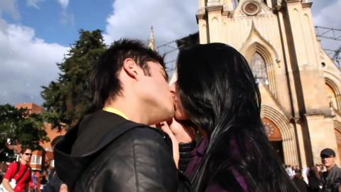 Una parjea joven se besa en un parque frente a una iglesia.