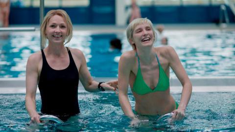 Dos mujeres sonríen en una piscina.