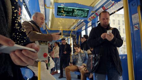 En el interior de un autobús, pasajeros revisan sus teléfono móviles.