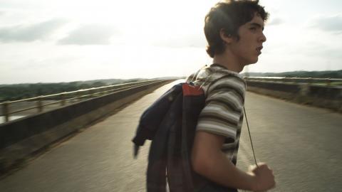 Un joven con una mochila cruza un puente.