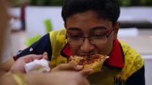 Joven comiendo pizza.