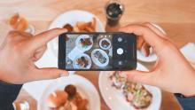 Joven tomando foto de su plato con su celular