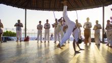 Un grupo de jóvenes practica capoeira en una terraza al atardecer.