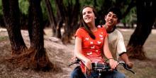 Dos adolescentes sonríen montados en una motocicleta.