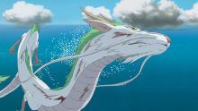Un dragón blanco y turquesa vuela encima del mar.