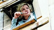 Una mujer se lava los dientes y se asoma en la ventana de una casa de árbol en la película alemana Out on a limb